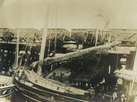 明治半ば大牟田川で小舟に石炭を積み込む様子